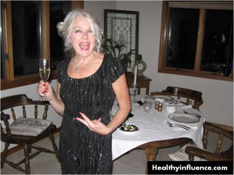 older white woman holding champagne glass while flashing gang sign