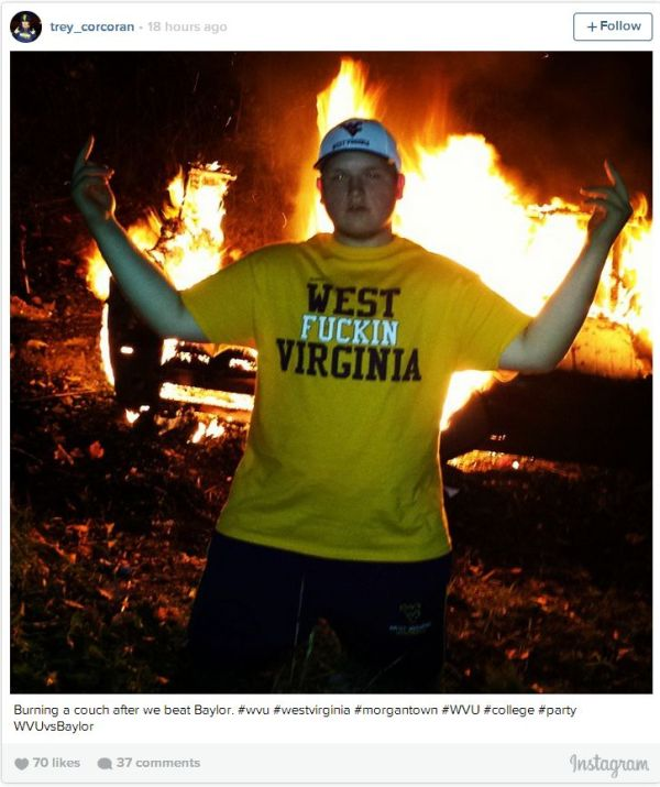 West Virginia Student in front of burning couch after football team's win over Baylor