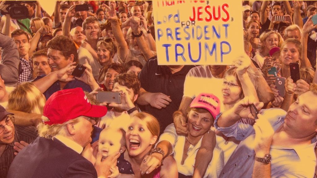 "President Donald Trump greets supporters while one supporter holds a sign that says ""Thank you Lord Jesus for President Trump."""