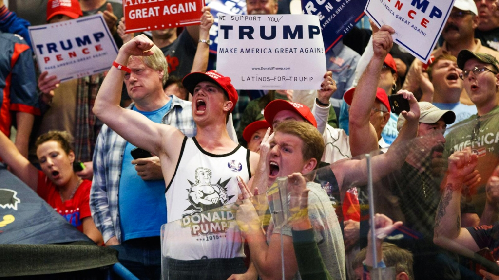 """trump supporters at rally. some are holding """"make america great again"""" signs."""